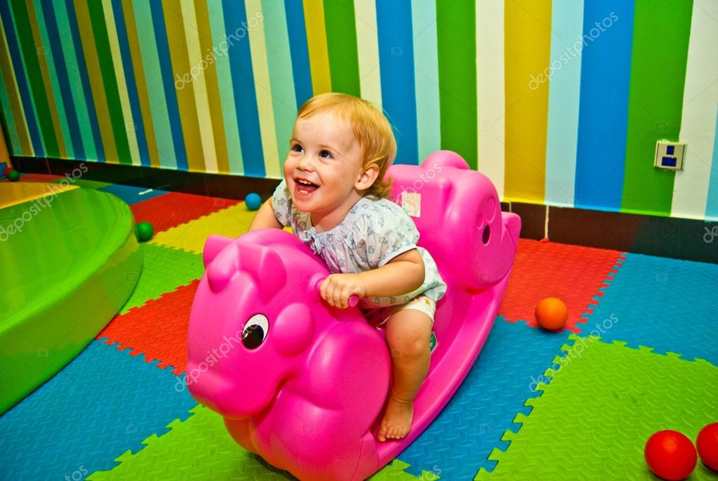 Girl 1,5 year old swinging on a pink rocking horse