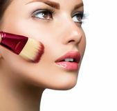 Fotografia cosmetico. base per il trucco perfetto. applicare il make-up