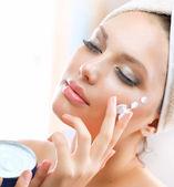 Fotografie Beautiful Young Woman applying facial moisturizing cream