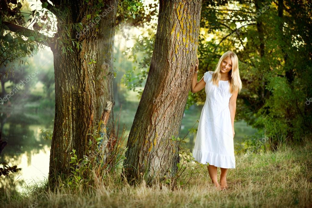 Beautiful girl in fairy forest near the river