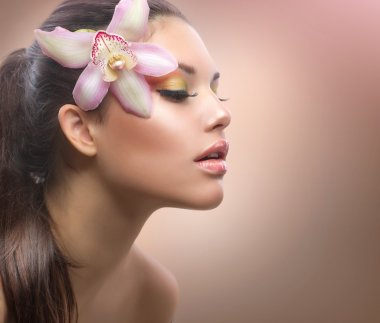 Beauty Portrait. Beautiful Stylish Girl with Orchid Flower