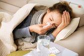 Fotografie Kranke Frau. Grippe. Frau erkältet. Niesen ins Gewebe