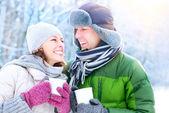 Fotografie glückliches Paar mit heißen Getränken im Freien. Winterurlaub