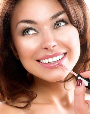 Beauty Girl Applying Lipgloss. Makeup. Beautiful Woman's Face