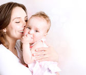Fotografie Mother and Baby kissing and hugging. Happy Family
