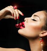 Szexi nő étkezési cseresznye. Érzéki ajkak piros cseresznye