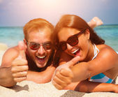 Fotografie Happy Couple in Sunglasses having fun on the Beach