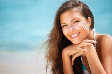 Beautiful happy Girl applying Sun Tan Cream on her Face