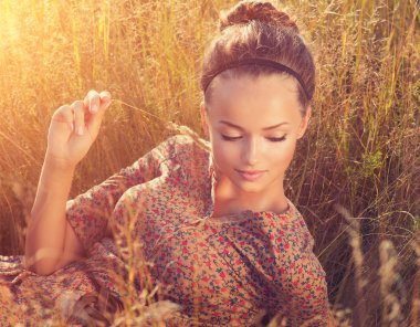 Beauty Romantic Girl Lying on the Field in Sun Light
