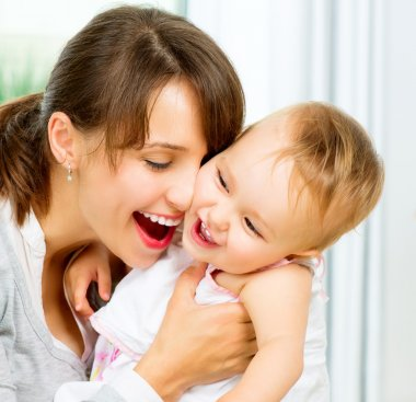 Happy Smiling Mother and Baby kissing and hugging at Home