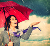 Fotografie Lächeln Frau mit Regenschirm über Herbst regen Hintergrund