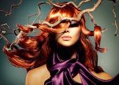 Módní model žena portrét s dlouhými kudrnatými vlasy červené