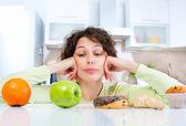 dietu koncept. mladá žena, volba mezi ovoce a sladkosti