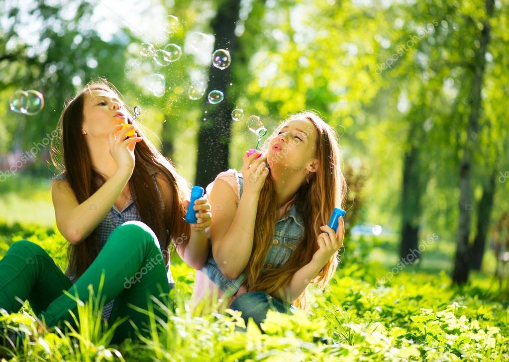 Teenage girls blowing soap bubbles