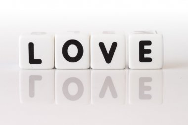 The word love spelled in game dice reflected on isolated white background. stock vector