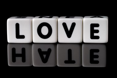 Love spelled in dice with the word hate reflected on black isolated background stock vector