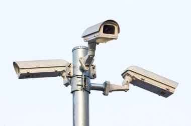 Three security cameras against the blue sky.