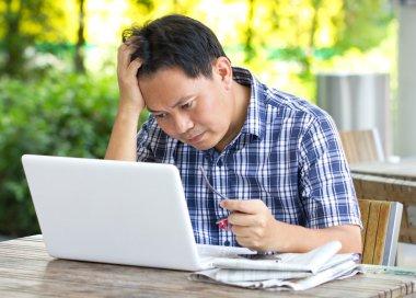 Stress Asian man looking at laptop.