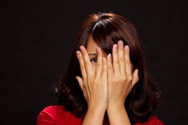 Woman hiding her face through hands