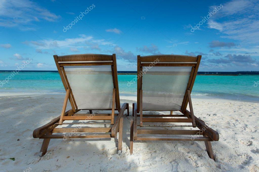 Beach chairs on tropical beach.