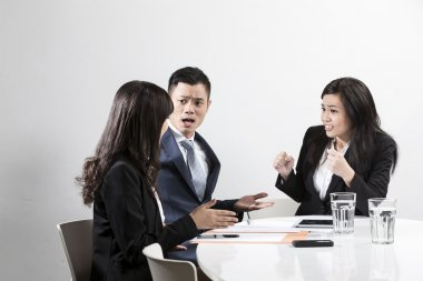 Chinese business team shouting at each other in business meeting