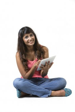 Young woman sitting on floor using a Digital Tablet PC.