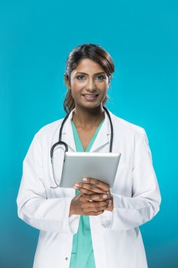 Portrait of a Female indian, doctor holding a digital tablet.