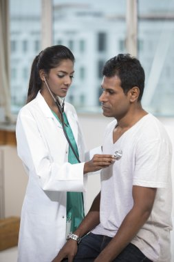 Indian doctor doing a check up on male patient.
