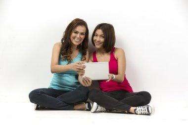 Two happy Asian women using a digital tablet.