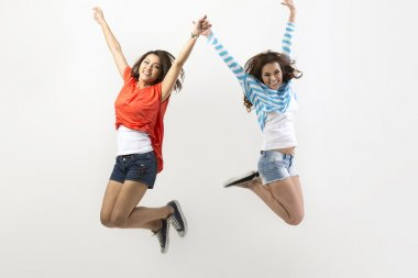 Two excited Asian women jumping in front of a white wall. stock vector