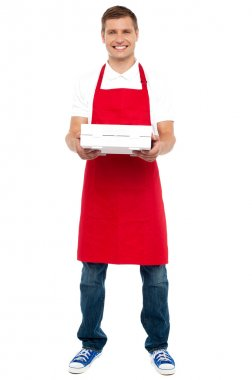 Full length portrait of male chef holding pie box
