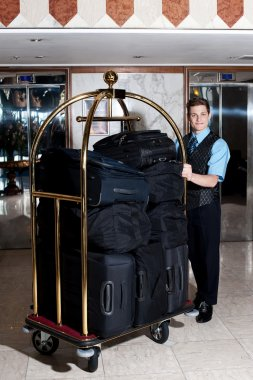 Bell boy pushing cart loaded with luggage