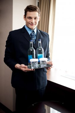 Male butler holding fresh beverages for customers