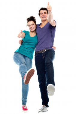 Teen love couple enjoying themselves, gesturing thumbs up