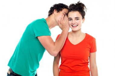 Handsome boy talking secret to young girl in her ear