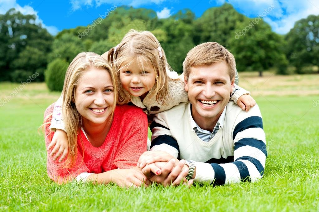 Happy young family with daughter outdoors