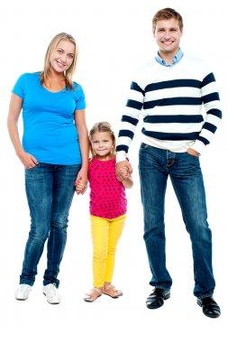Sweet little kid standing in between her parents