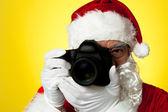 Fotografie Aged Santa adjusting camera lens before click