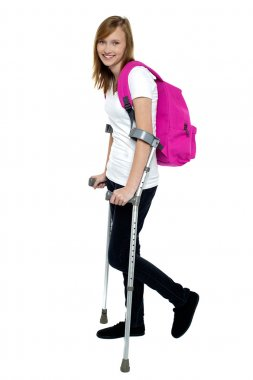 University student walking with help of crutches