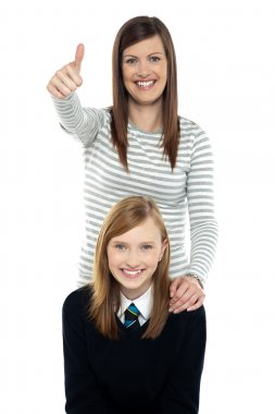 Cute schoolgirl with her mom. Mother gesturing thumbs up