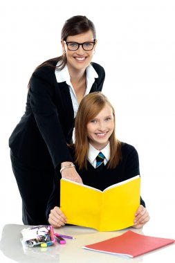 Teacher instructing student and helping her