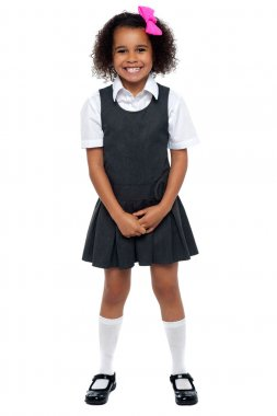 Cheerful young kid in pinafore dress posing smilingly