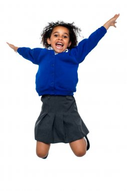Jubilant school kid jumping high up in the air