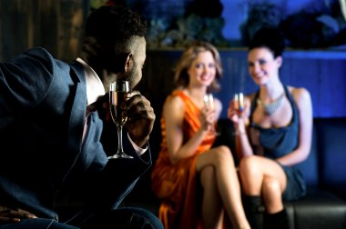 Elegant man looking at hot young girls in nightclub