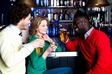 Group of three friends in a bar drinking beer