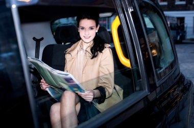Female passenger reading newspaper inside taxi