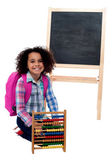 Photo Happy school girl with abacus and pink backpack