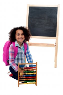 Happy school girl with abacus and pink backpack