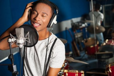 Young male singer in recording studio stock vector