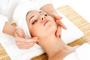 Woman getting facial massage in spa salon